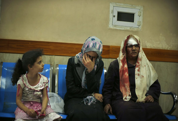 A Palestinian woman reacts as she sits next to another woman, who medics said was wounded during heavy Israeli shelling at the Shejaia district, at a hospital in Gaza City
